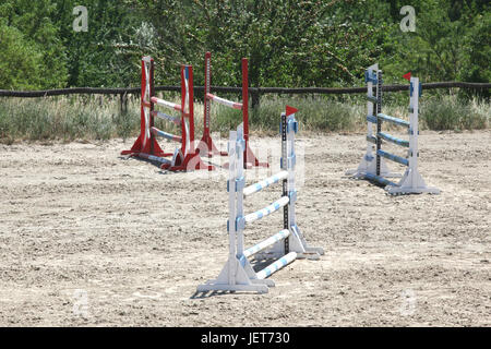 Colorful wooden barriers on the ground for jumping horses and riders - Stock Photo