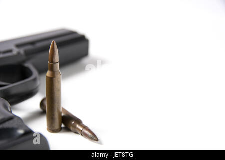 Hand gun sitting with m-16 bullets isolated on white background. - Stock Photo