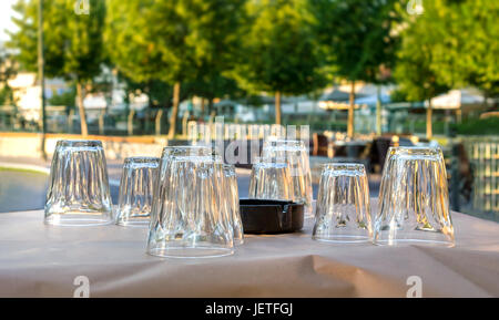 A greek tavern dinning table with paper tablecloth , transparent glasses and ashtray. - Stock Photo