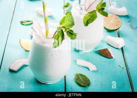 Summer refreshment drinks, cocktails. Frozen coconut mojito with lime and mint. Pina colada. On a light blue green - Stock Photo