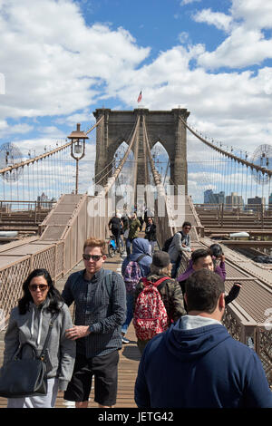 people walking over the brooklyn bridge New York City USA - Stock Photo