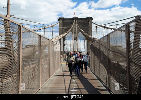 people walking over the brooklyn bridge between cables New York City USA - Stock Photo