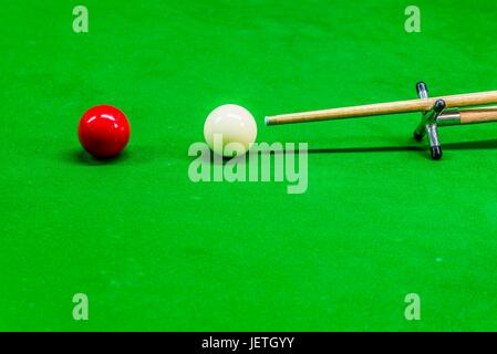 White Cue ball and red ball with a cue on a rest - Stock Photo