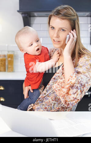 Busy Mother With Baby Coping With Stressful Day At Home - Stock Photo
