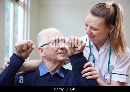 Nurse Assessing Stroke Victim By Raising Arms - Stock Photo