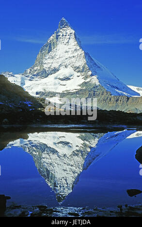 Matterhorn is reflected in a mountain lake, Matterhorn spiegelt sich in einem Bergsee - Stock Photo