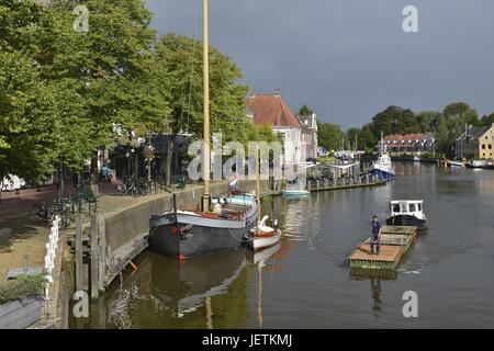 Work pontoon and two boats on the water of the canal Het Grootdiep in Dokkum's historic district under a dark sky, - Stock Photo