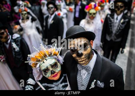 Young couples, costumed as La Catrina, a Mexican pop culture icon representing the Death, walk through the town - Stock Photo
