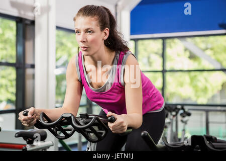 Woman working out on exercise bike - Stock Photo