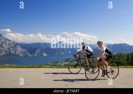 Man and woman with the racing wheel in alpine scenery, Mann und Frau mit dem Rennrad in alpiner Landschaft - Stock Photo
