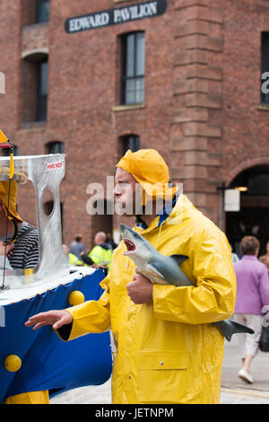 Men dressed as trawlermen in a toy boat and carrying a plastic shark to entertain the public at an outdoor event - Stock Photo