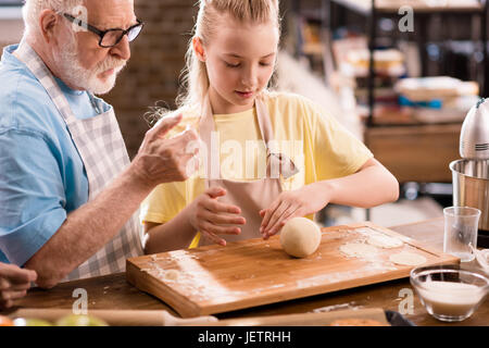 grandfather and granddaughter cooking and kneading dough for cookies at kitchen table, cooking in kitchen concept - Stock Photo