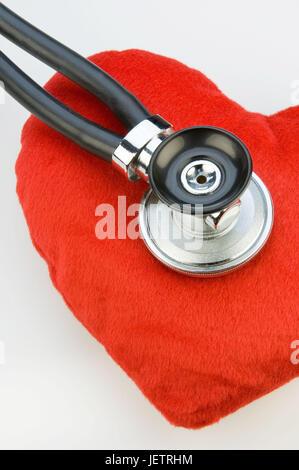 Stethoskop monitors a material heart, Stethoskop hoert ein Stoffherz ab - Stock Photo