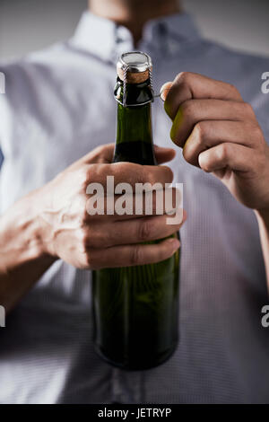 closeup of a young caucasian opening a bottle of champagne - Stock Photo