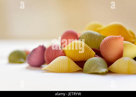 closeup of a pile of uncooked conchiglie, italian seashell pasta, with different colors: yellow as usual, red made - Stock Photo