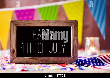 a wooden-framed chalkboard with the text happy 4th of july written in it and an American flag, placed on a rustic - Stock Photo