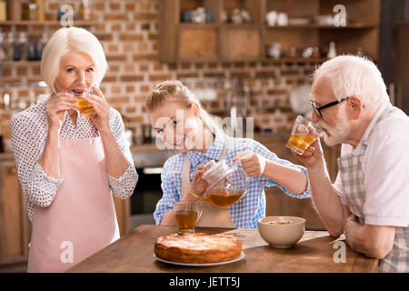 grandparents and girl drinking tea with pie together at home - Stock Photo