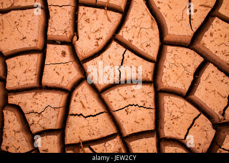 Desert cracks in dry, red clay - Stock Photo