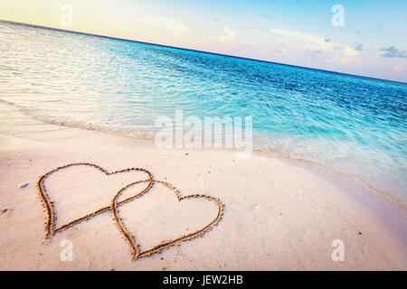Two hearts drawn on sand of a tropical beach at sunset. Clear turquoise ocean. Maldives islands. - Stock Photo