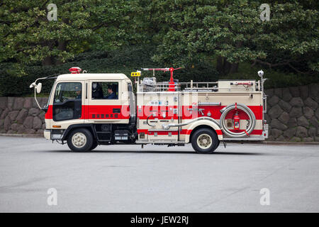 TOKYO, JAPAN - CIRCA APR, 2013: Japanese fire-truck with firefighters drives in streets of the Tokyo city. Traditional red colored car of rescue and f