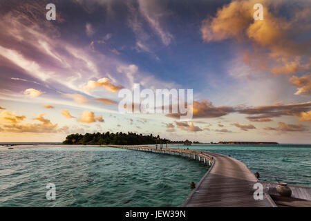 Wooden jetty towards a small island on Indian Ocean, Maldives at sunset - Stock Photo