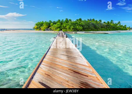 Wooden jetty towards a small island on Indian Ocean, Maldives. Sunny blue sky. - Stock Photo