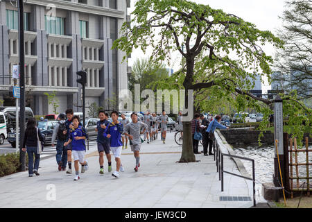 TOKYO, JAPAN - CIRCA APR, 2013: Japanese youths jog through the city center. Schoolboys training is on urban streets. - Stock Photo
