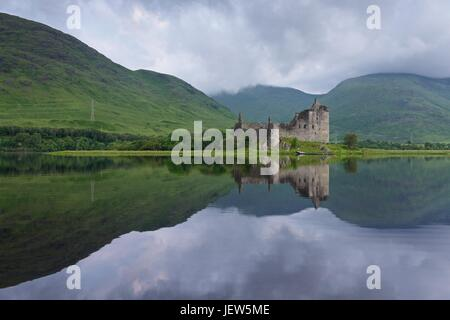 Reflections on an overcast morning of the ruins of Kilchurn Castle. The image was taken from the banks of Loch Awe - Stock Photo