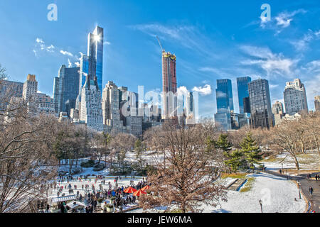 Central Park and Skyline in Winter with Ice Rink and Snow - Stock Photo