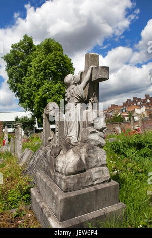 LONDON, ENGLAND - JULY 12, 2017 Gravestones in Tower Hamlets Cemetery Park London. Girl clinging to the cross - Stock Photo