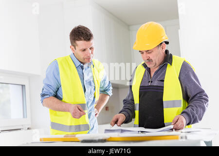 Architect and construction engineer indoor meeting. Building experts cooperation and project analysis. Real estate - Stock Photo