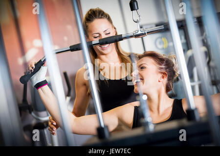 Personal trainer helps with gym equipment workout. Two attractive women training, building strength. Sport concept. - Stock Photo