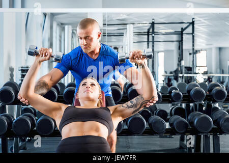 Personal trainer corrects and motivates while bodybuilding training at the gym. Professional help during workout. - Stock Photo
