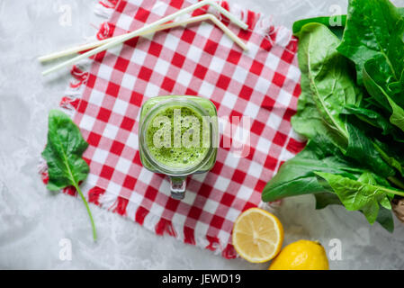 Top view Healthy green spinach smoothie in a jar mug with ingredients on the checkered napkin on the white marble - Stock Photo