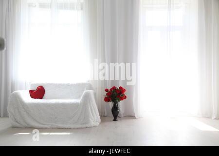 Interior white room sofa flowers light from the window - Stock Photo