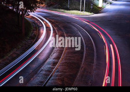 Bend of the road with tram rails in the light of street lamps with a trace from the lights of passing cars - Stock Photo