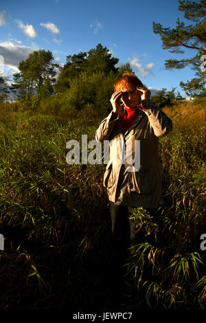 The mature, red-haired woman in glasses. - Stock Photo