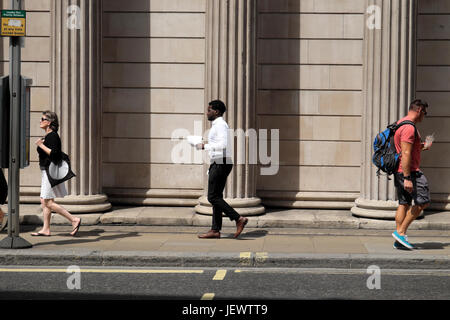 People walking along the street outside the Bank of England columns on Threadneedle Street in financial district - Stock Photo