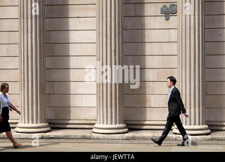 Business people walking along the street outside the Bank of England on Threadneedle Street in financial district - Stock Photo