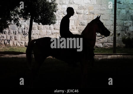 Jerusalem, Israel. 28th June, 2017. A young Arab man rides a horse near the Old City walls. Credit: Nir Alon/Alamy - Stock Photo