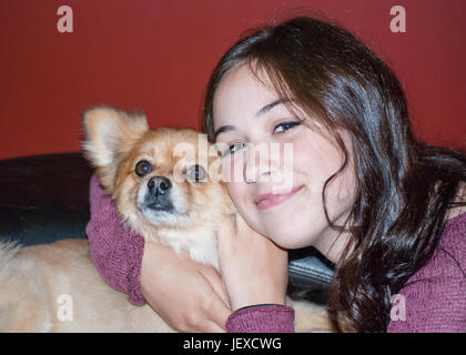 Girl holding dog with a smile - Stock Photo
