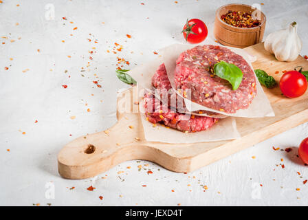 Fresh raw home-made minced beef steak burger with spices, tomatoes and basil, on a white stone concrete table, copy - Stock Photo