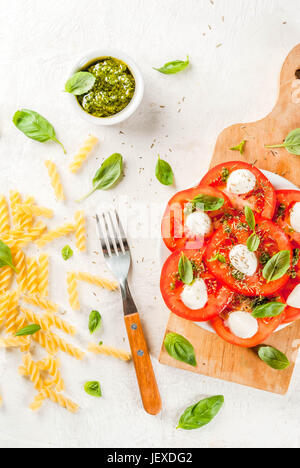 Italian food. Spring dinner for one person. Salad caprese - tomatoes, mozzarella cheese, fresh and dried herbs, - Stock Photo