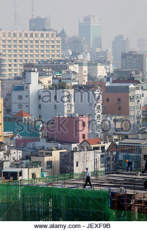 A foreman walks through a construction site in Ho Chi Minh City. - Stock Photo