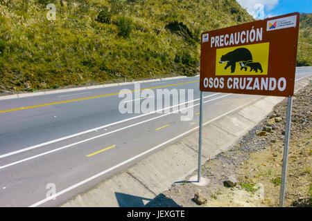 QUITO, ECUADOR - AUGUST 8, 2014: Informative sign to aware the crossing of bears in Papallacta, in a beautiful landscape - Stock Photo