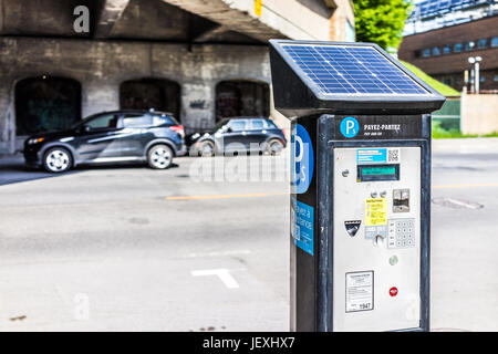 Montreal, Canada - May 28, 2017: Paid car street parking in downtown city in Quebec region with solar panel - Stock Photo