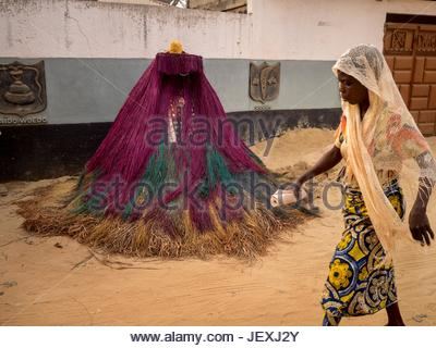 A woman walking in front of a Zangbeto mask, known as a 'Nightwatchman,' the traditional voodoo guardian of the - Stock Photo