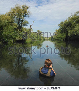 Wildlife photographer, Bertie Gregory, photographing a great crested grebe, Podiceps cristatus, while submerged - Stock Photo