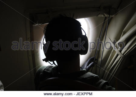 A member of the Japan Maritime Self Defense Force looks out of the window of a PC3 reconnaissance plane. - Stock Photo