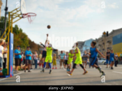 Teenagers playing  basketball on the street. Lens blur - Stock Photo